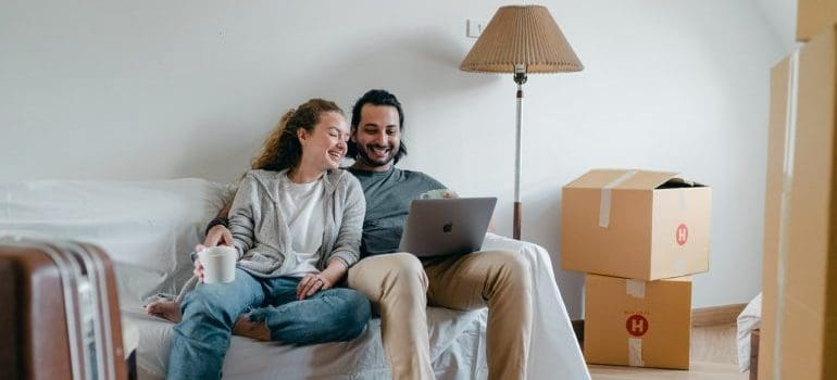 Couple spending time together on a sofa after moving