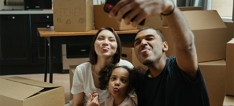 A family taking pictures with packed boxes, enjoying their move
