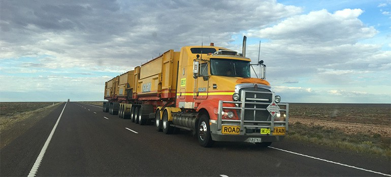 A big yellow truck on a clear road
