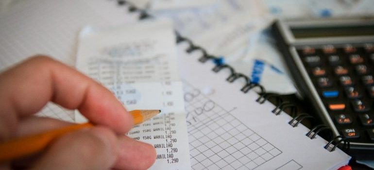 Calculating expenses on a paper with the calculator