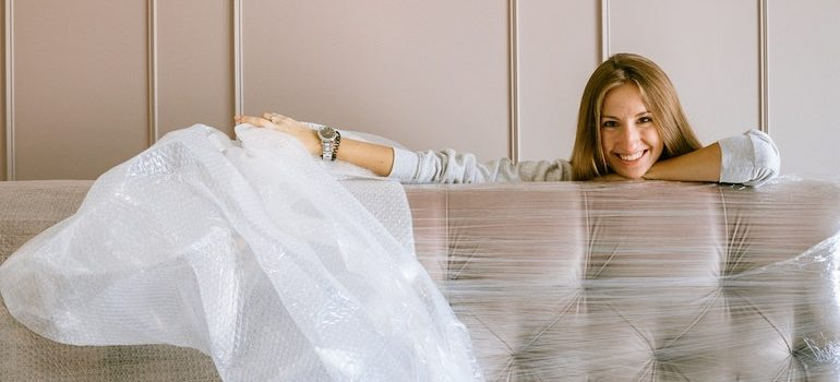 woman behind the sofa removing plastic wrapping