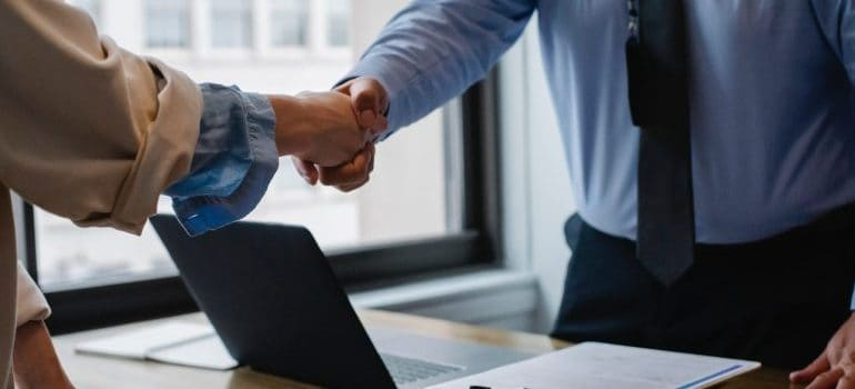 Man and a woman hand shaking after making a deal